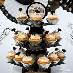 """A cupcake tower is the sweetest way to say """"Congrats Grad!"""" Bake your favorite cupcakes in silver foil baking cups & top them with grad cap party picks, then stack them into each tier of your cupcake tower. Done!"""