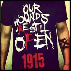 """Tee shirt commemorating the Armenian Genocide of 1915. Lyrics from R-Mean's song """"Open Wounds"""" printed on the front along with the year. """"Our Wounds Are Still Open 1915"""""""