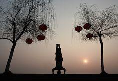 Suining, China: A man performs morning exercises near a riverbank.    Photograph: AP