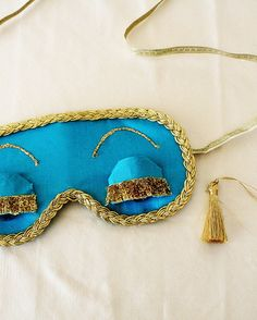Don flats, a men's white tuxedo shirt or button-down, and a pair of shorts underneath.Gold upholstery tassels can be strung through earplugs to stick in your ears. Split your hair into pigtails and add Holly's DIY sleep mask for the complete look.