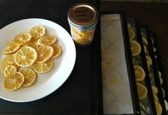 Dehydrated lemon slices on a plate, in a jar and on dehydration trays.