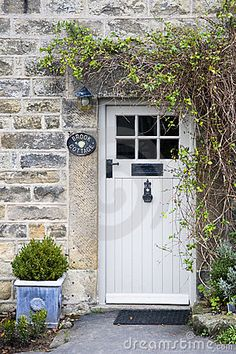 Photo about Old stone cottage with white stable door and small window to the side, two small conifers in terracotta pots either side of the door. Image of cottage, terracotta, building - 23624062 Cottage Front Doors, Front Door Porch, Cottage Windows, House Doors, House Front, Country Front Door, Cottage Front Garden, Cottage Style Doors, Door Entryway