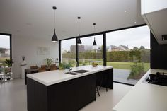 Nieuwbouw vrijstaande woning – Ypsilon architecten, keukeneiland - witte gietvloer - driedelig schuifraam Timber Ceiling, Floor To Ceiling Windows, Exterior Design, Interior And Exterior, Timber Dining Table, Black Kitchens, Concrete Floors, White Walls, Bungalow