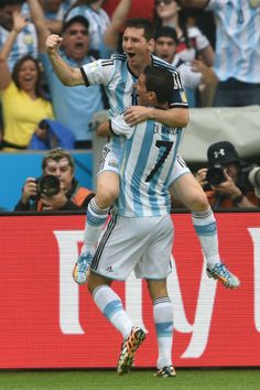 Let Lionel Messi Show You What A Perfect Free Kick Goal Looks Like - Argentina's forward Lionel Messi (L) celebrates his goal with midfielder Angel Di Maria (C), during a Group F football match between Nigeria and Argentina at the Beira-Rio Stadium in Porto Alegre during the 2014 FIFA World Cup on June 25, 2014.