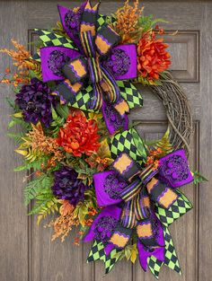 This Halloween wreath with the combination of fall florals and gorgeous Halloween ribbon makes a statement! This gorgeous Halloween wreath will look fabulous hanging on your front door or above your mantel for fall all the way through Halloween.