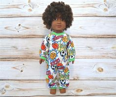 18 inch boy doll or girl doll american made flannel pajamas sleepwear. This pair is a fun sports print with colors of white, black, orange and lime green. It features basketballs, soccer balls, and footballs.  The flannel pajama pants have lime green pulled cotton knit cuffs and waistband.  The flannel shirt has a pulled cotton knit collar and cuffs and closes in the back with soft hook and loop strips.   I lay out the front of the shirts on the fabric, to keep the design the same or very…