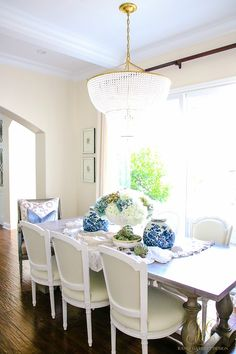That beaded chandelier though! Buttermilk leather chairs at a farmhouse table dressed for autumn with ruffled linens and blue ginger jars. Fresh Ideas for Fall Home Tour - Elegant Fall Decor - Randi Garrett Design