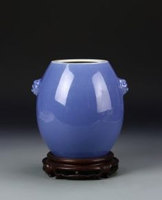 China, 19th Century, blue glazed vase with bulbous form. Light blue in color, with small, face-like decorations on either side. Base and interior unglazed, wooden stand included. Height 7 1/4 in., Diameter 7 1/2 in.