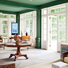 I probably would never do this - but there is something fascinating about the dark green walls against bright white french style windows with a view of other, natural greenery.