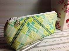 This bright and cheerful plaid 100% cotton fabric, is yellow, green, and teal. Padded and fully lined.  The shape of the case is sleek with curved corners at the top towards the zipper for a secure side-to-side closing. The bottom of the case has a flat bottom that allows it to stand on its on. It measures 9.00 inches wide (23 cm) and 4.0 inches tall (10.2 cm), and 1.5 inches across the bottom (3.8 cm).