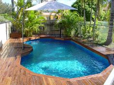 Grecian in-ground pool designs with wooden deck and iron railing umbrella