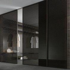 Modern walk-in dressing room with black semi-transparent sliding doors