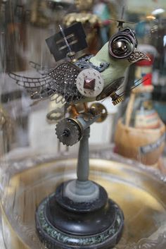 """Steam Punk Sparrow Awaiting Flight  Denise was inspired by other artist's bird creations and had so much fun creating this little guy  from vintage and new metal embellishments. The ironic thing was that she unknowingly picked a vintage tray  to display him onthat isengraved from the 1960's and reads""""Head Vulture"""""""