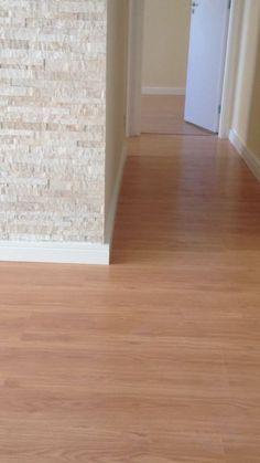 Sala com piso laminado com rodapé branco, revestimento estilo canjiquinha na parede do home