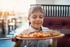 Stock Photo : Little boy smelling pizza in restaurant