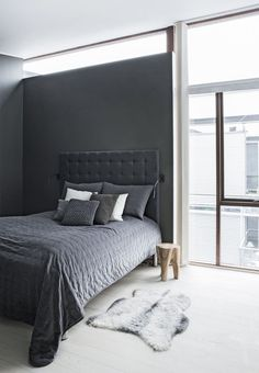 The dark grey walls gives this bedroom a cave-like feel - cozy and elegant. The headboard is by Tine K, the pillows and the blanket from Massimo.