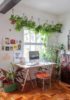Home Office tem mesa de cavalete, cadeira de ferro e varal com espécies de plantas variadas.