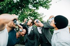 Groom and his boys shotgunning beers at a reception.  photo by: TGTB COLLECTIVE  Tacoma wedding photographers rustic barn wedding: The Mason Jar