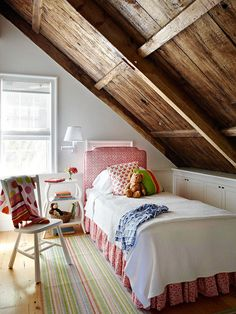 A twin bed tucks under the second-story eaves of the an 1817 farmhouse. Wood plank ceilings enhance the bedroom's warm, sweet style.