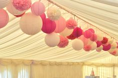 Perfect pinks! Paper lantern and pom pom canopy in a marquee in Buckinghamshire. By Oakwood Events