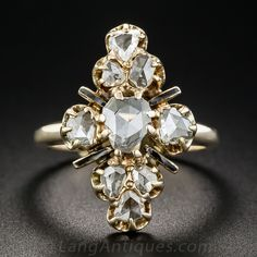 We rarely come across rose-cut diamond dinner rings, and this 7/8 inch long and lovely Victorian-era (circa 1875) sparkler is a stunning example. Nine asymmetrically shaped rose-cut diamonds, totaling 1.25 carats, glitter atop a navette shape crown accented with black enamel rays. A rare beauty. Hand-fabricated in sturdy 10K rosy-yellow gold, currently ring size 6 1/4.