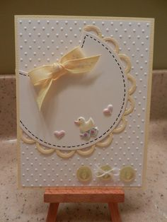 Cut this adorable bib from a circle, with a scallop punch edging in your color of choice.  Add a bow and duck or other embellishments, and place the whole thing on top of swiss dotted paper.  Buttons tied with twine finish off this great handmade baby card.