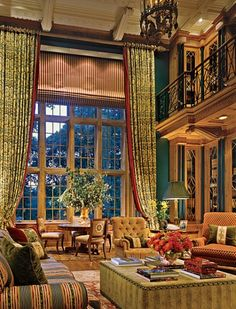 pretty amazing room ~ long panels 'warm' high ceilings; leaded glass doors on cabinets, colors, iron railing!