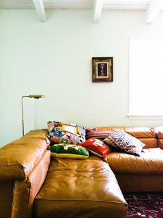 Lush tan leather corner lounge, eclectic cushions & cool mint toned walls. Love.