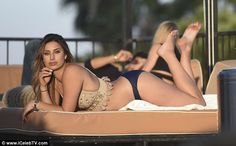 Taking it easy: The star seemed to be lost in her own little world as she set to work topping up her tan on one of the sun loungers by the pool