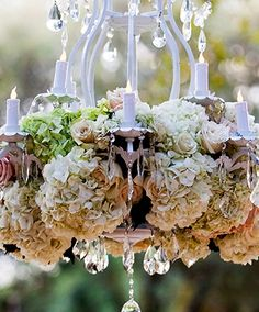 A crystal chandelier, adorned with lush hydrangeas and roses, is the perfect way to add a touch of classic elegance to an outdoor ceremony.