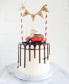 Chocolate drip on a semi naked chocolate cake topped with macarons, red toy car and bunting caketopper