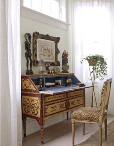 An Italian painted desk makes the side hall into a usable room rather than a pass-through space.