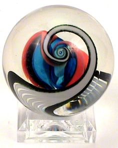 These hand made glass marble by Fritz Art Glass Studios (Fritz Lauenstein) make a great gift for the marble collector in your family. Or maybe even adding them to your own collection.They are 2 Inches in diameter and come with a small clear acrylic base to display them on.Made in the USA by Fritz Lauenstein.