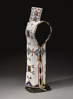 SIOUX BEADED HIDE CRADLE of typical construction, the sack, thread and sinew-sewn in opaque and translucent glass beadwork, with concentric rectangular devices alternating with diamond designs, the opening edged with striped panels, surmounted by a rectangular tab with additional beaded details; lined with printed cotton cloth.