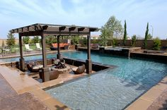 Custom lounge/patio area set below pool level to create a 3-sided waterfall effect