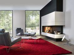 Houthaard met liftdeur in modern interieur. Dit moderne interieur heeft een mooie balans van elegante en stoere elementen. De robuuste stoelen en het ruige rode vloerkleed combineren prachtig met de elegante tafel, de grote ramen en de design haard. De haard is voorzien van een liftdeur en dat zorgt voor een optimale verbranding. Wil je genieten van het knappend haardvuur, dan zet je de liftdeur gewoon open waardoor je optimaal zicht hebt op de vlammen.