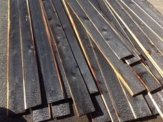 Once I had the surface fully burnt, I laid them down, clipped the wire and extinguished the fire.  I had to use a blow torch to touch up the areas along the edge that didn't get charred.  I have seen some people use a roofer's torch to blacken the surface, then brush off the soot and apply Penofin, but I wanted the full charcoal layer.