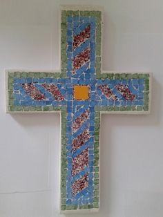 Σταυρός χειροποίητος με ψηφίδες κεραμικές,τεχνητές κ.λ. Συγκρατείται εσωτερικά με μεταλλικό πλέγμα και έχει προεξοχή μεταλλική για κρέμασμα. Διαστάσεις 0,29Χ0,20Χ0,01 cm).
