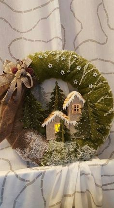 Beautiful felt wreath with tiny lit up miniature houses. Love the moss and lichen look!