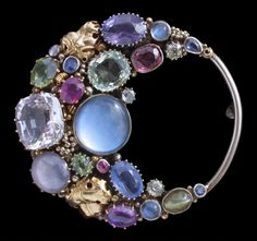 Dorrie Nossiter. Arts and Crafts brooch, open elliptical circular/crescent form. Silver, gold, sapphire, moonstone, peridot, garnet, chrysoberyl and ruby, c. 1930. Sold by Tadema Gallery. View 2.