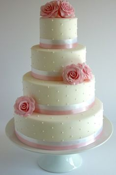 """Fairytale Rose & Pearl Pink Wedding Cake with handmade sugar roses and piped royal icing pearls. 4"""" and 6"""" Vanilla sponge with strawberry preserve and vanilla buttercream. 8"""" and 10"""" Lemon sponge with lemon curd buttercream. As shown £410, serves 130 finger portions/ 80 dessert portions."""