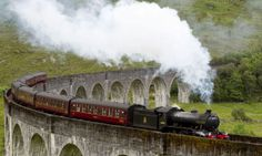 The Jacobite steam train passing over the Glenfinnan Viaduct, Lochaber District in Scotland.  This is the train that they used for the Harry Potter movies.