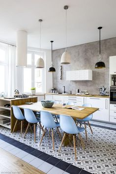 The kitchen is simply white, with light colored wood countertops and light blue chairs