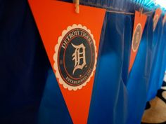 Detroit Tigers baby shower theme.  Detroit Tigers orange and blue. Pennant flags. Hand made. Decals cut with punch press from Michaels. Mini clothes pins and twine from Michaels.