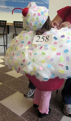 Cupcake costume. Upside down lamp shade and cotton batting.Could just do it as a large prop without the kid :)