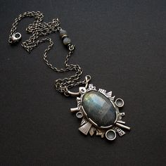 Unique necklace hand formed out of silver, adorned with a lovely cabochone of…