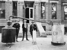 Three Larimer County Officers are shown in front of the sheriff's office in the old courthouse, with results of a raid on a moonshiner's illegal whiskey still.  June 1, 1927