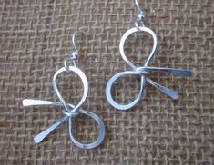 Handcrafted here at Bantam Lake Studio, these adorable Bow Earrings are made of 16 guage Sterling Silver wire which are formed and shaped, then hammered in some areas to accentuate the shape. They measure 1 wide x .80high. Being handcrafted, each one may vary slightly. French earring