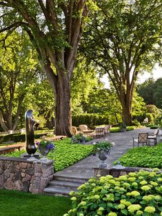 Stone Escape - Huge shade trees. Pachysandra. White Hydrangea. Stone hardscaping. Nooks for seating.