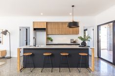 Kitchen from AMC Spec Home 4. Black traceless laminate base cupboards, drawer fronts and on the back of the island bench.  American oak legs on the island bench, 20mm caesarstone benchtop and timber look laminate to overhead cupboards.